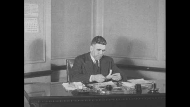 Young man at pencil sharpener / fade General Manager / fade to man at desk who circles January 1 1937 on calendar which is then superimposed on the...