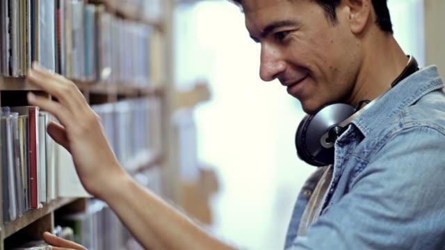 4 k: レコード店で若い男 - ミュージックショップ点の映像素材/bロール