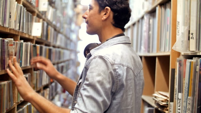4k: young man at record store - following moving activity stock videos & royalty-free footage