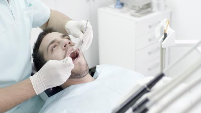 junger mann im zahnarzt - zahnarzt stock-videos und b-roll-filmmaterial