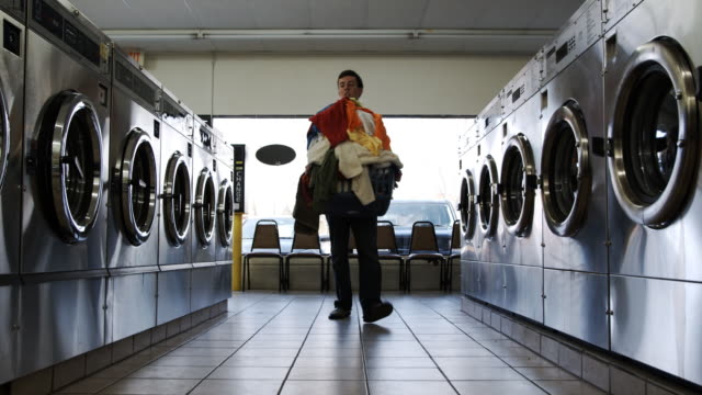 young man at the laundromat - waschsalon stock-videos und b-roll-filmmaterial