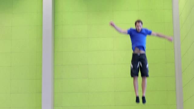Junger Mann Athleten springen auf dem Trampolin