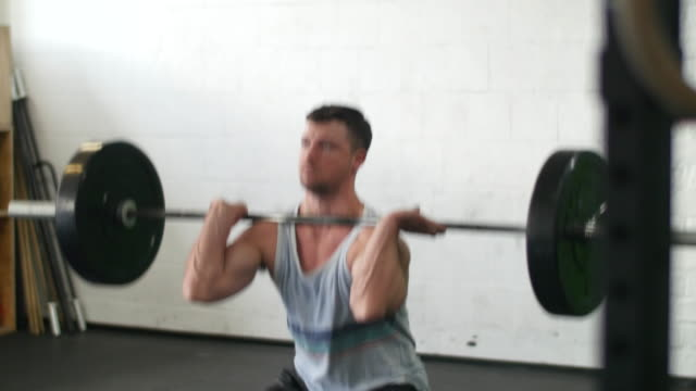 Young man athlete lifting weights