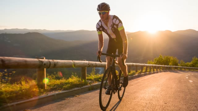 young man athlete standing while road cycling uphill, illuminated by sunlight - racing bicycle stock videos and b-roll footage