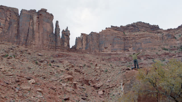 young man atop rocky outcrop spreads arms while taking in the splendor of the rugged moab landscape. - butte rocky outcrop stock videos & royalty-free footage