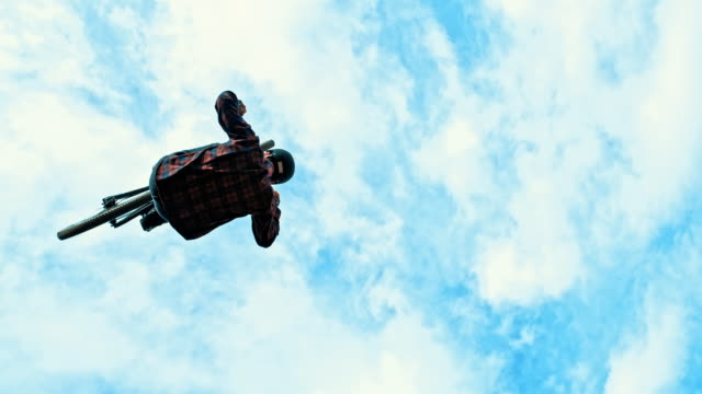 ms young man backflipping bmx bicycle against blue sky with clouds - inquadratura dal basso video stock e b–roll