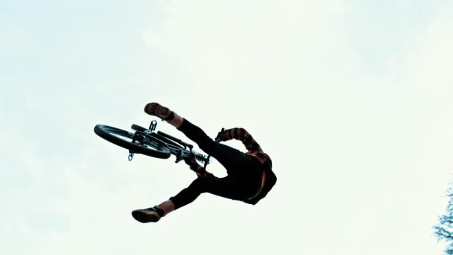 曇り空に対して ms 若い男 backflipping bmx の自転車 - 離れ技点の映像素材/bロール