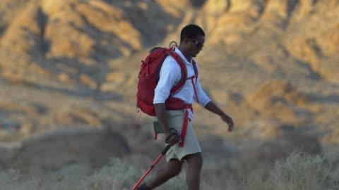 vidéos et rushes de a young man backpacking in a mountainous desert. - seulement des jeunes hommes