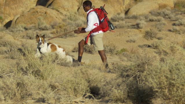 vidéos et rushes de a young man backpacking in a mountainous desert with his dog. - seulement des jeunes hommes
