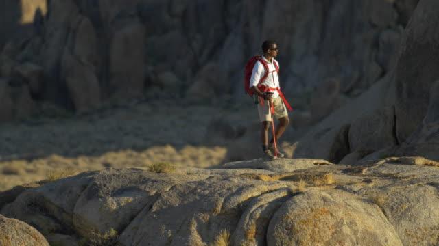 vidéos et rushes de a young man backpacking over boulders in a mountainous desert. - seulement des jeunes hommes