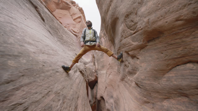 Young man balances over sandstone slot canyon with legs spread.