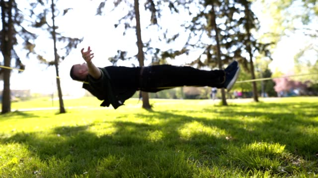 young man balancing lying on a slackline - zen like stock videos & royalty-free footage