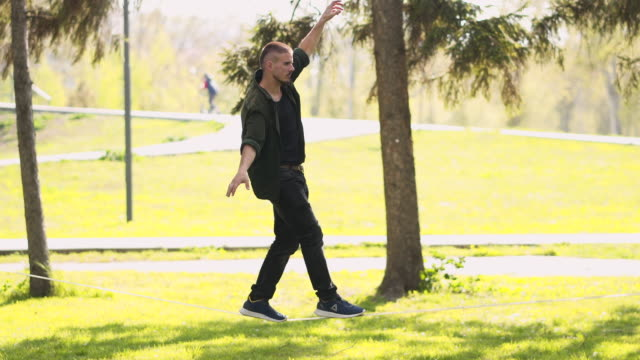young man balancing on a slackline - tightrope walking stock videos & royalty-free footage
