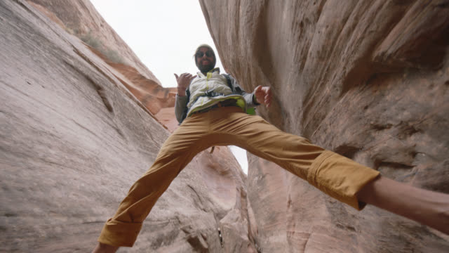 Young man balancing over sandstone slot canyon looks down at camera and makes shaka sign.