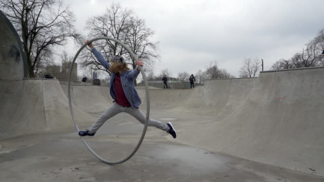 A young man balancing with a Cyr wheel