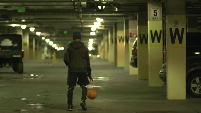 vidéos et rushes de a young man basketball player dribbling a basketball in a parking garage. - slow motion - lettre de l'alphabet
