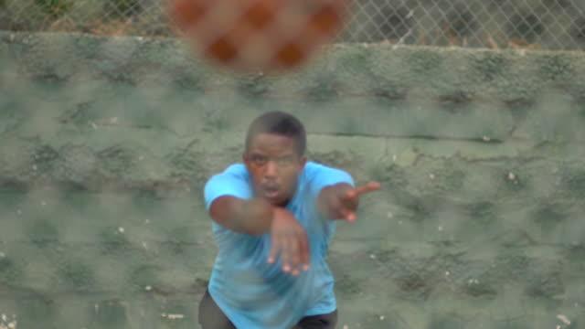 a young man basketball player dribbling before passing the ball to a teammate. - slow motion - korta ärmar bildbanksvideor och videomaterial från bakom kulisserna