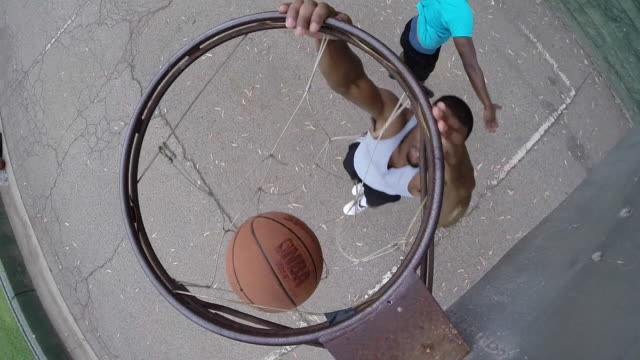 A young man basketball player dunking while playing one on one on a street basketball court.