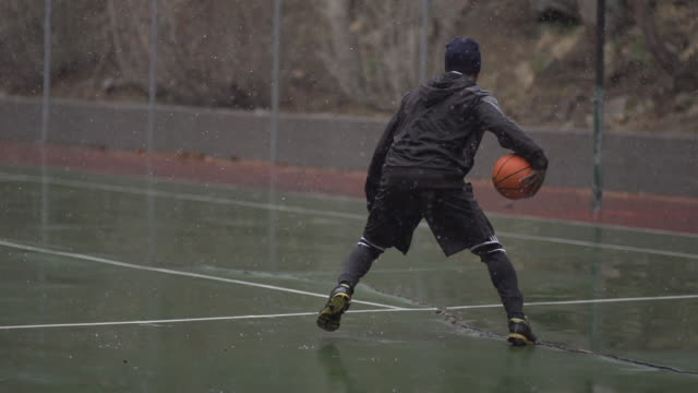a young man basketball player practicing his ball handling outdoors in the freezing rain. - super slow motion - filmed at 240 fps - sports field stock videos and b-roll footage