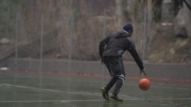 A young man basketball player practicing his ball handling outdoors in the freezing rain. - Slow Motion