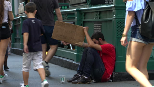 A young man begs for money outside of the Wall Street Station subway stop / He holds a handwritten cardboard sign reading 'STARTED TO GIVE UP STILL...