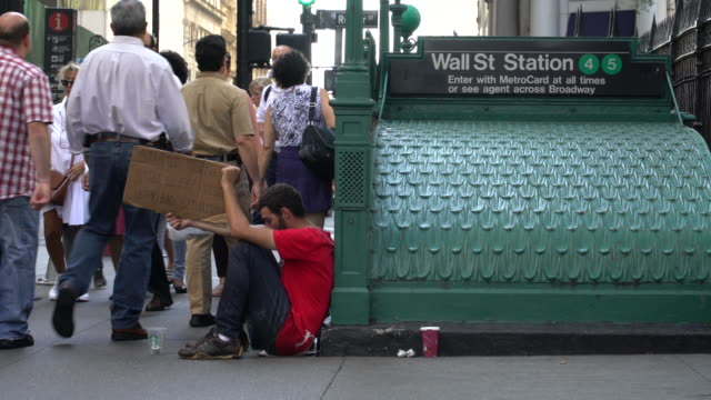 """young man begs for money outside of the wall street station subway stop / he holds a hand-written cardboard sign reading """"started to give up still... - crisi video stock e b–roll"""