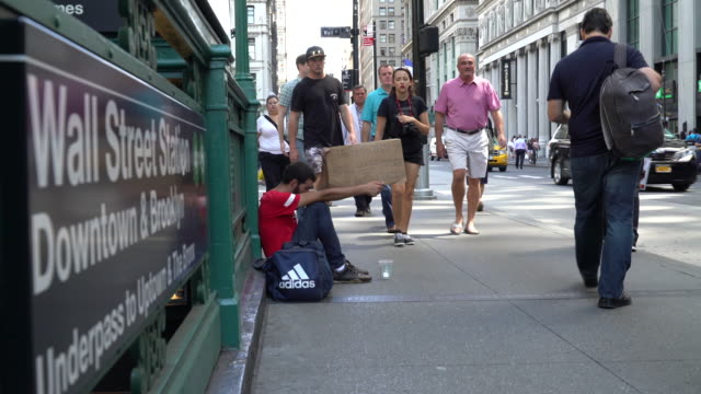 vídeos de stock, filmes e b-roll de a young man begs for money outside of the wall street station subway stop / he holds a handwritten cardboard sign reading started to give up still... - mendigo