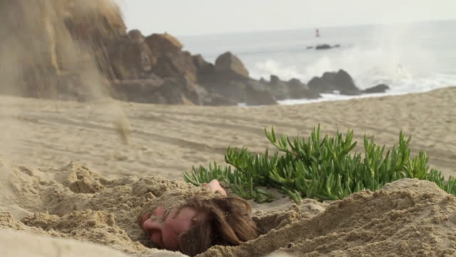 vídeos de stock e filmes b-roll de ms shaky young man being buried on beach / los angeles, california, usa - enterrado