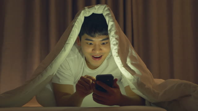 a young man being happy after using the mobile phone in the room - 喜び点の映像素材/bロール