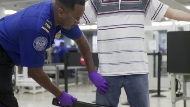 ms young man being searched by airport security / jacksonville, florida, usa - säkerhetsskanner bildbanksvideor och videomaterial från bakom kulisserna