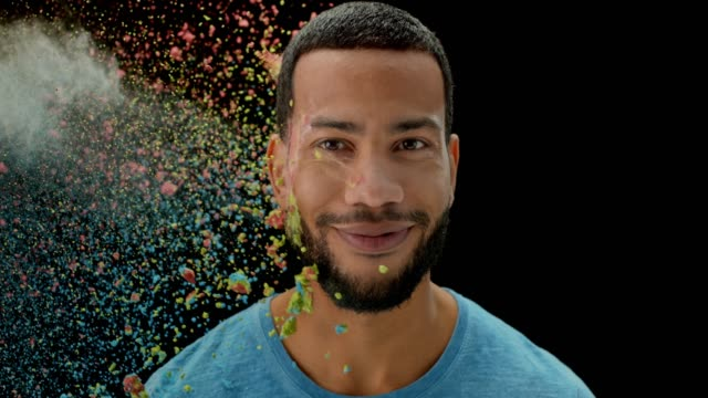 slo mo young man being thrown multi colored powder dust into the face  and opening his mouth in surprise - powder paint stock videos & royalty-free footage