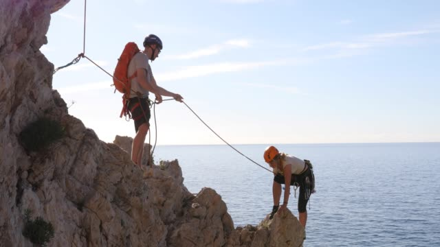 young man belays young woman on rock climb, above sea - belaying stock videos & royalty-free footage