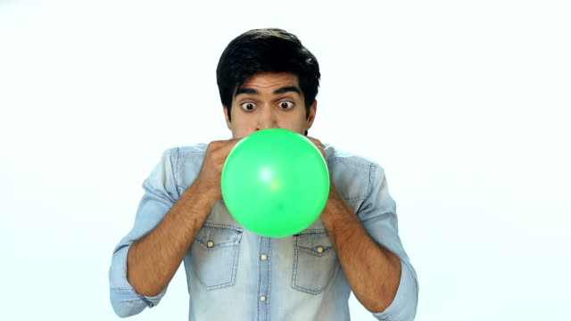 vídeos de stock, filmes e b-roll de ms young man blowing balloon - enchendo
