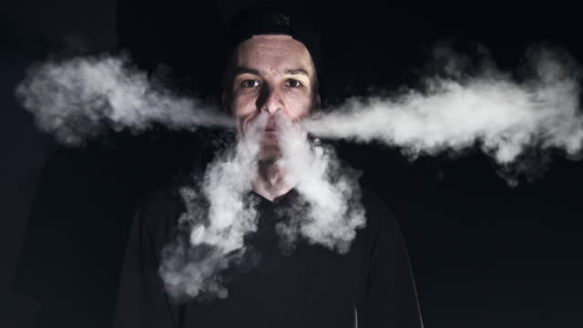 MS Young man blowing vapour from the E-Cigarette