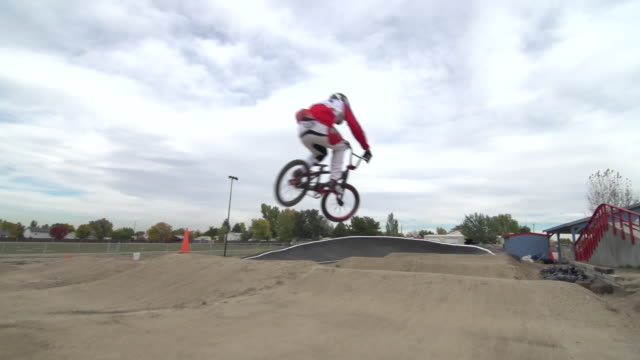 a young man bmx rider riding on a dirt track. - freestyle bmx stock videos and b-roll footage
