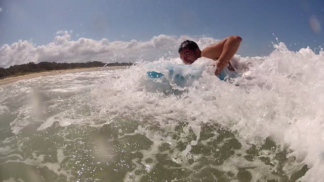 Young man bodyboarding in Byron Bay, Wategos Beach, long shot