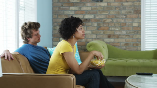 young man bored and agitated while his date watches tv