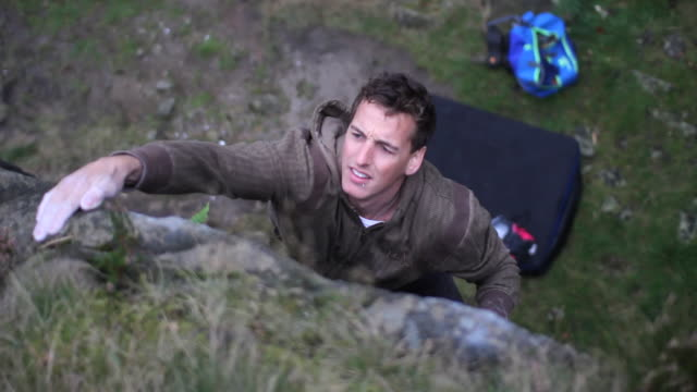 A young man bouldering.  - filmed in Hebden Bridge, Yorkshire, England, Europe