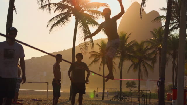 young man bouncing and spinning on slackline - rio de janeiro stock videos & royalty-free footage