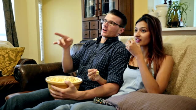 Young man brings bowl of popcorn to share with girlfriend while watching television together