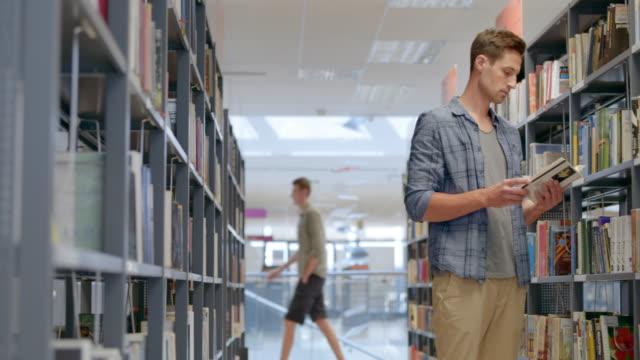 DS Young man doorbladert voor een boek in de bibliotheek