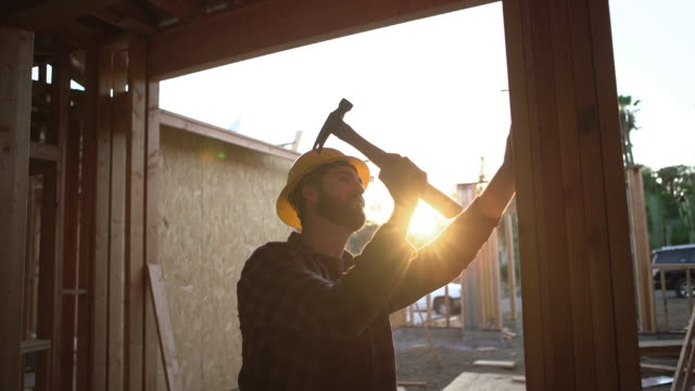 vidéos et rushes de cu young man building a house - plante