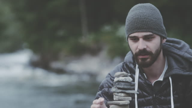 若い男の建物は川のそばの岩の塔。バランスを探してください。 - 石点の映像素材/bロール