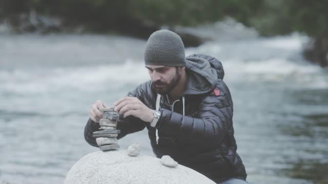 若い男の建物は川のそばの岩の塔。娯楽の追求 - 石点の映像素材/bロール