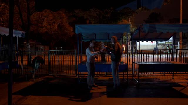 junger mann kauft covid-19-impfstoff-flasche auf dem schwarzmarkt von einem verdächtigen mann - marktstand stock-videos und b-roll-filmmaterial