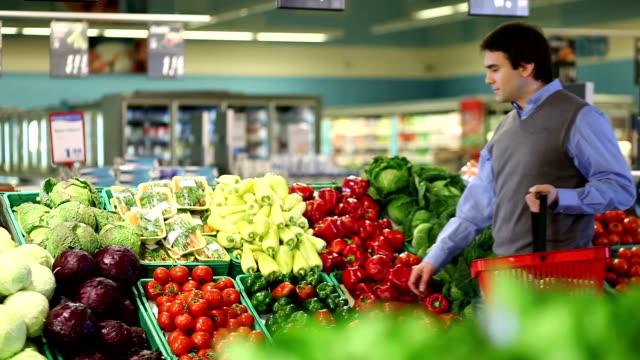 vídeos y material grabado en eventos de stock de hombre joven compra verduras - vegetal con hoja