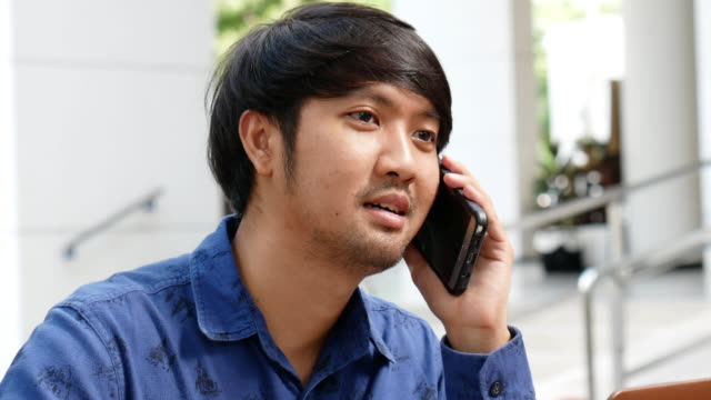Young Man Calling on Phone with Laptop