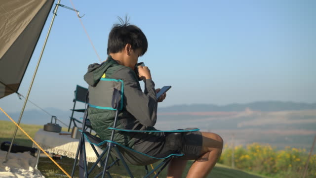 young man camping in mountain using his mobile phone - tent stock videos & royalty-free footage