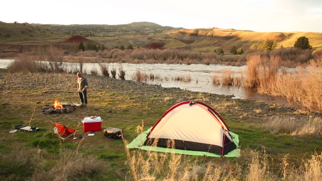 a young man camping in near a river with a fire burning and the sun setting. - zelt stock-videos und b-roll-filmmaterial