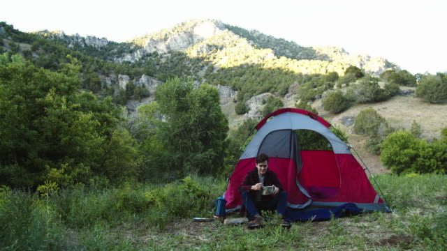 young man camping in the mountains - nur junge männer stock-videos und b-roll-filmmaterial